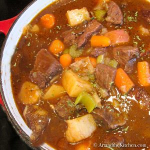 close up view of Irish stew with beef and vegetables in dutch oven pot.