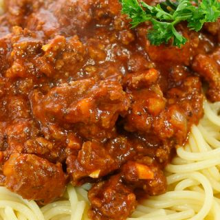 Thick meat sauce on spaghetti pasta with parsley sprig.