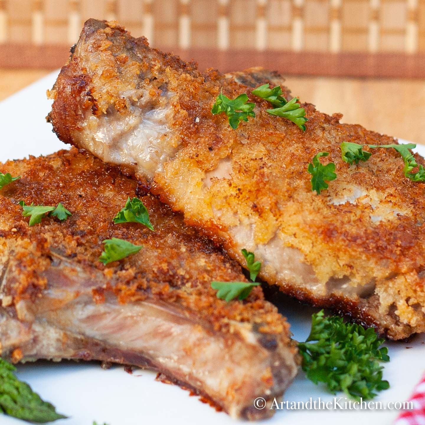 Two breaded pork chops fried golden brown on white plate.