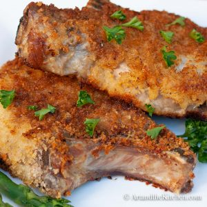 Two breaded pork chops fried to golden brown on white plate.