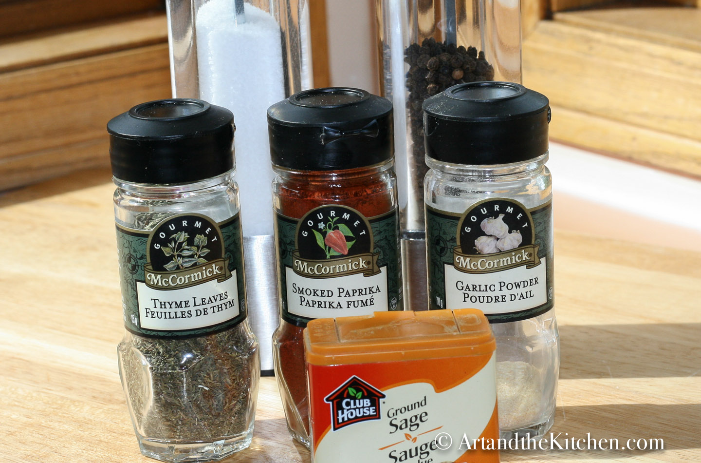 Bottles of spices, thyme, garlic powder, sage , smoked paprika with salt and pepper mills.