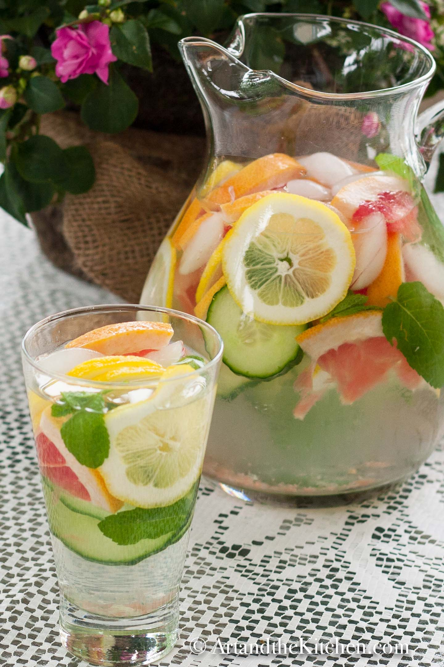 Glass pitcher and glass of water with slices of grapefruit, cucumber, lemon and mint.
