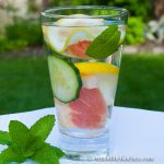 Glass of water with slices of grapefruit, cucumber, lemon and mint.