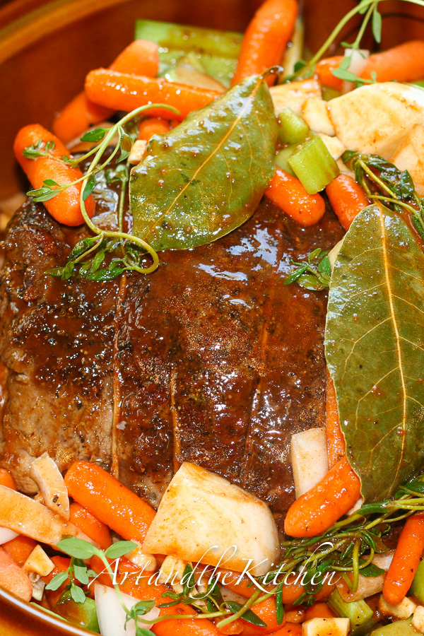 Roast beef with carrots, potatoes and bay leaves.