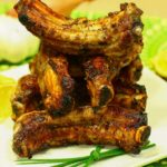 Stack of Greek marinated ribs with green onion sprigs and lemon slices