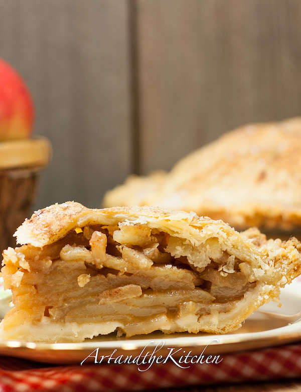 Apple pie with golden flaky crust on checkered cloth with basket of apples in background.