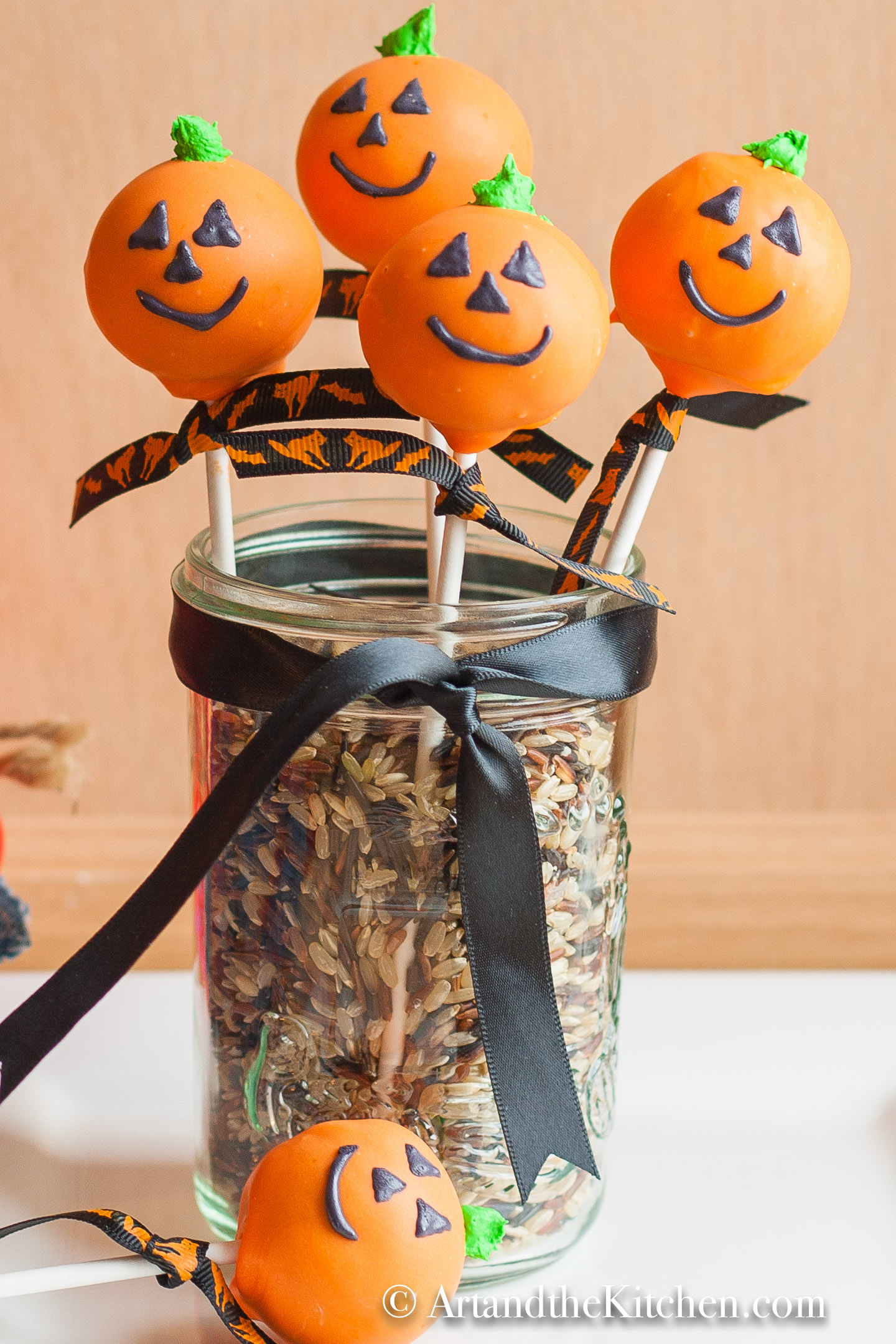 Five Jack O Lantern decorated cake pops in glass jar. Jar is filled with colored rice with a black ribbon tied around.