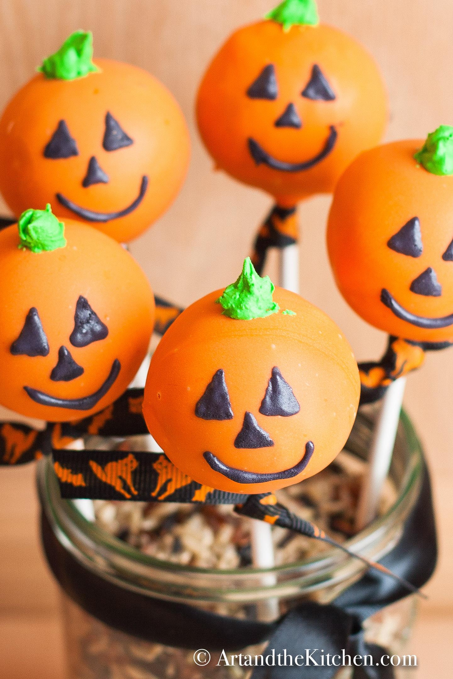 Five orange colored cake pops decorated like jack o lanterns displayed in a decorative jar.