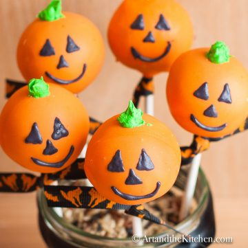 Five orange colored cake pops decorated like jack o lanterns displayed in a decorative jar.