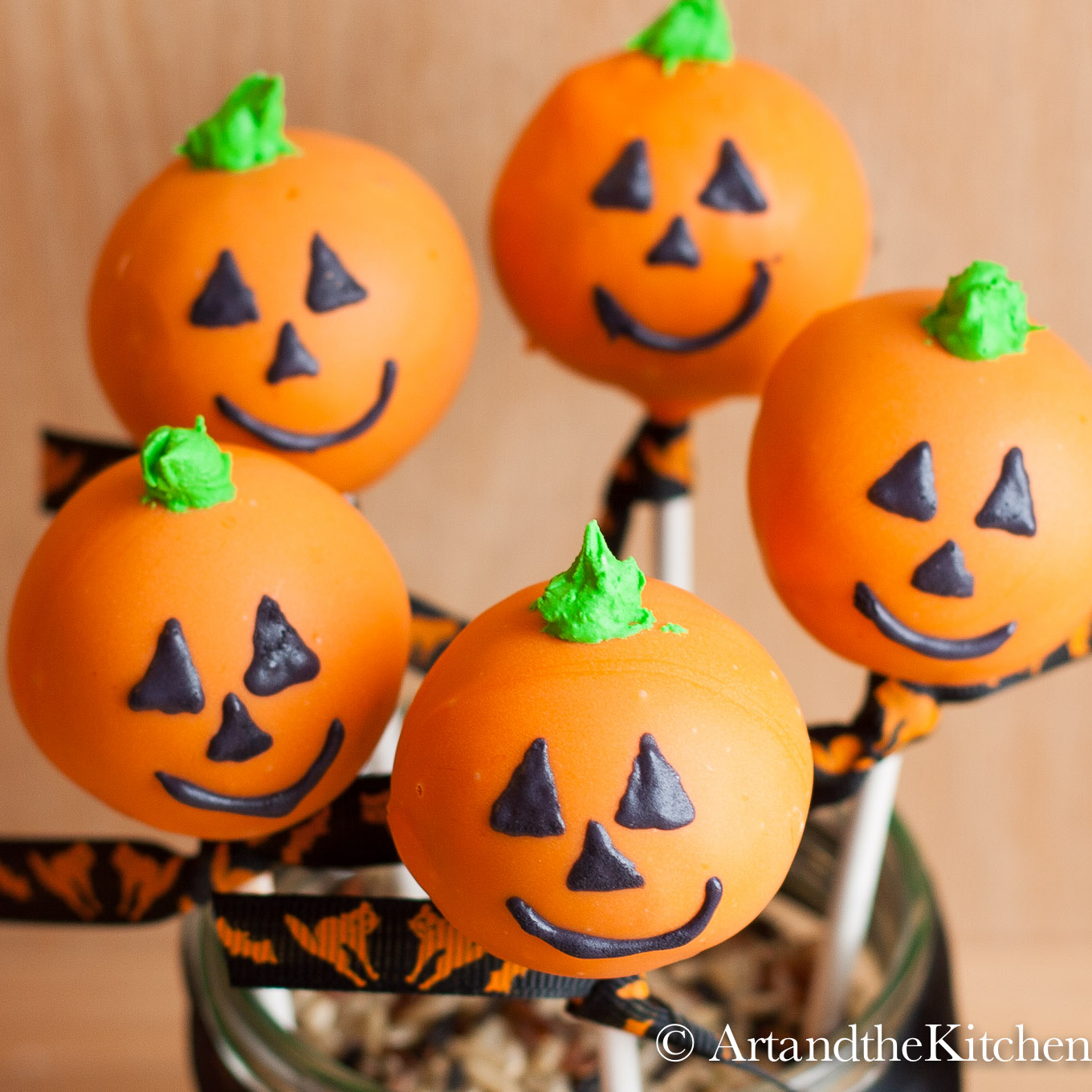 Five round cake pops that are decorated like Jack O Lanterns.