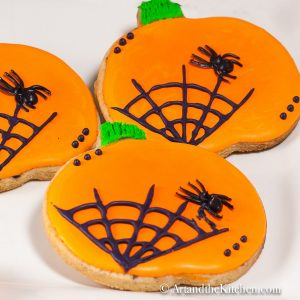 Pumpkin shaped sugar cookies decorated with orange icing and black spider web.