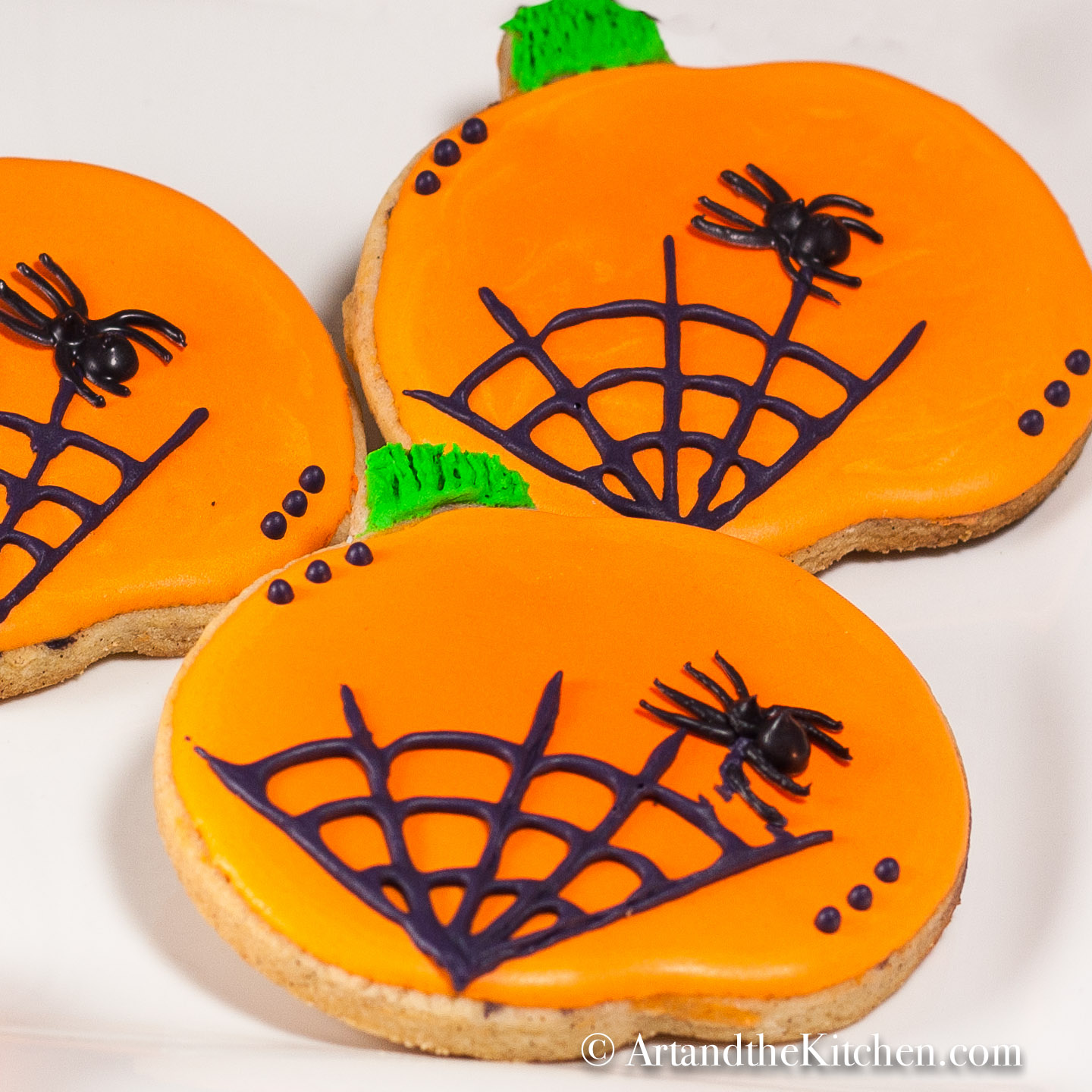 Three pumpkin shaped, orange frosted sugar cookies on a white plate. Decorated with black spider and web icing.