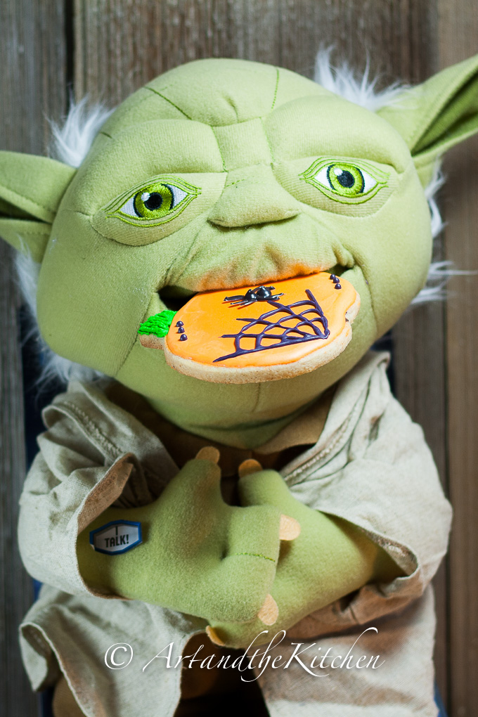 Plush Yoda doll eating an orange sugar cookie that is decorated with a spider web.