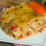 Slice of enchilada casserole made with leftover turkey, topped with a melted cheese layer.
