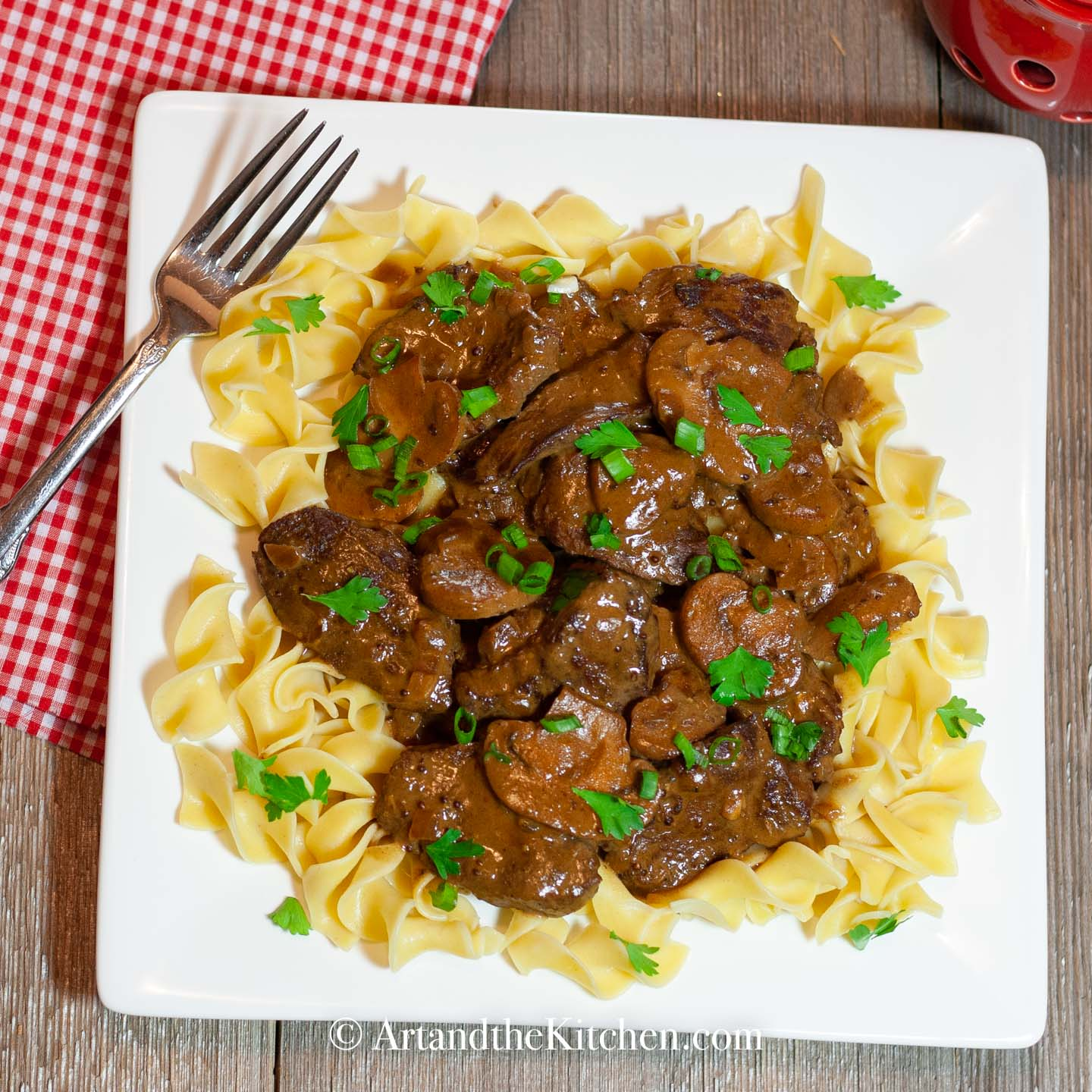 White square plate filled with beef stroganoff on a bed of broad noodles.