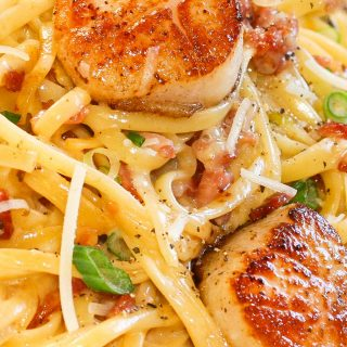 linguine pasta in a creamy carbonara sauce topped with pan seared scallops and green onion slices.