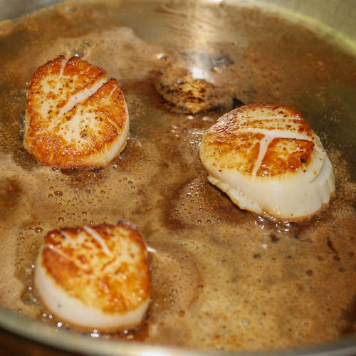 Three golden brown scallops frying in pan.