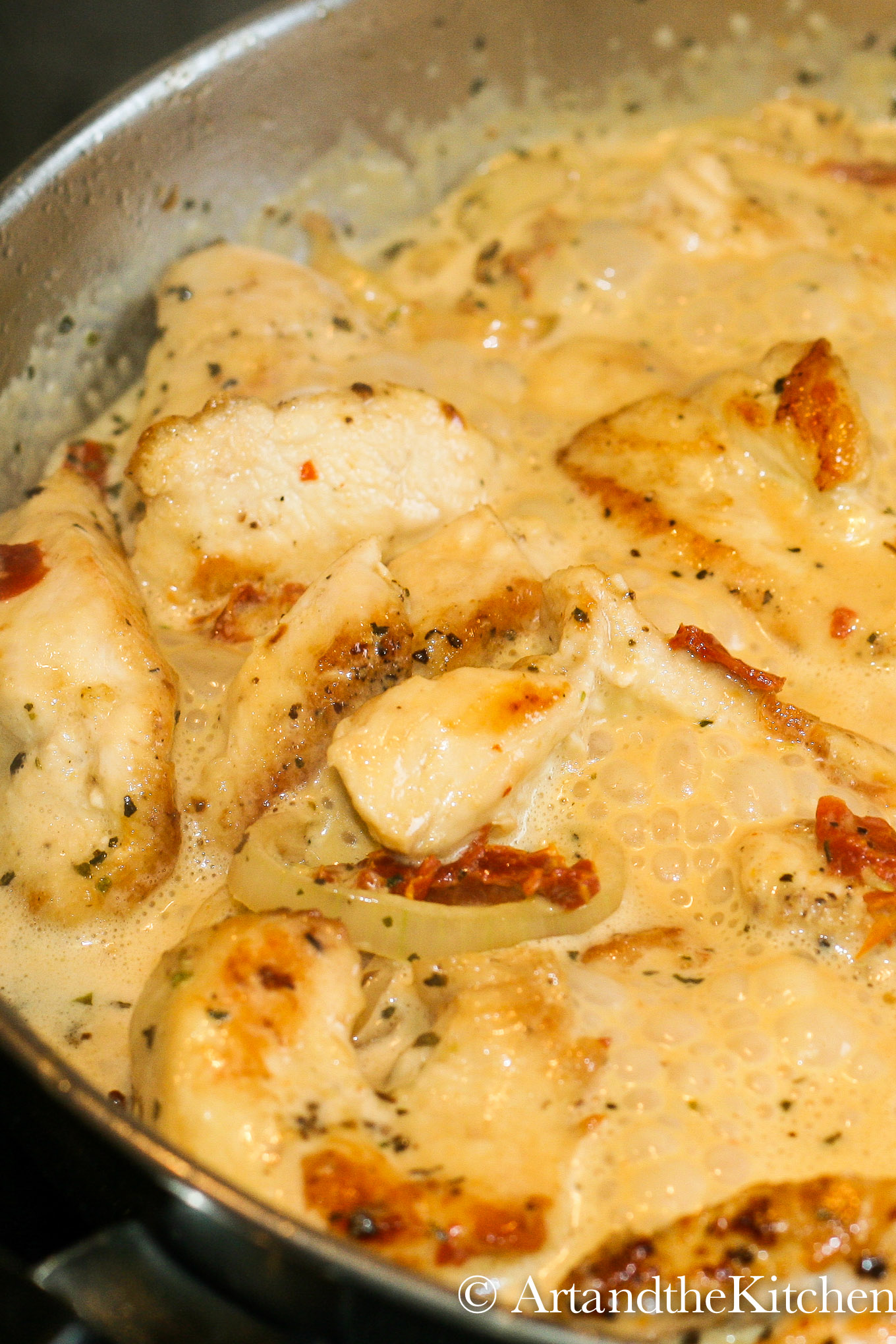 chicken with shallots and sun-dried tomatoes in a creamy sauce simmering in a stainless steel skillet.