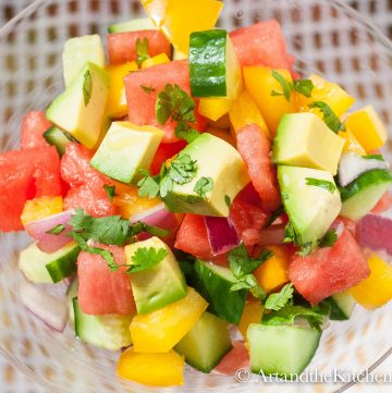 Salad of avocado, watermelon, cucumber, peppers, and red onions in glass bowl.