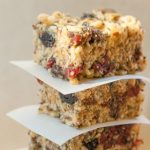 Stack of three homemade protein bars separated with parchment paper loaded with seeds and dry fruit