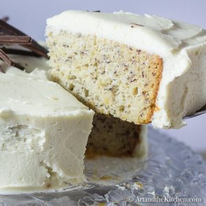 Slice of banana cake with layer of cream cheese frosting lifted from whole cake with cake server on a decorative glass plate.