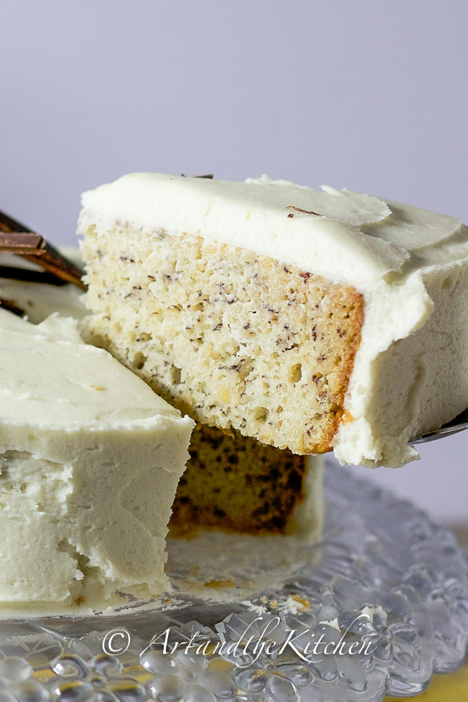 Slice of banana cake on cake server. Topped with layer of cream cheese frosting.