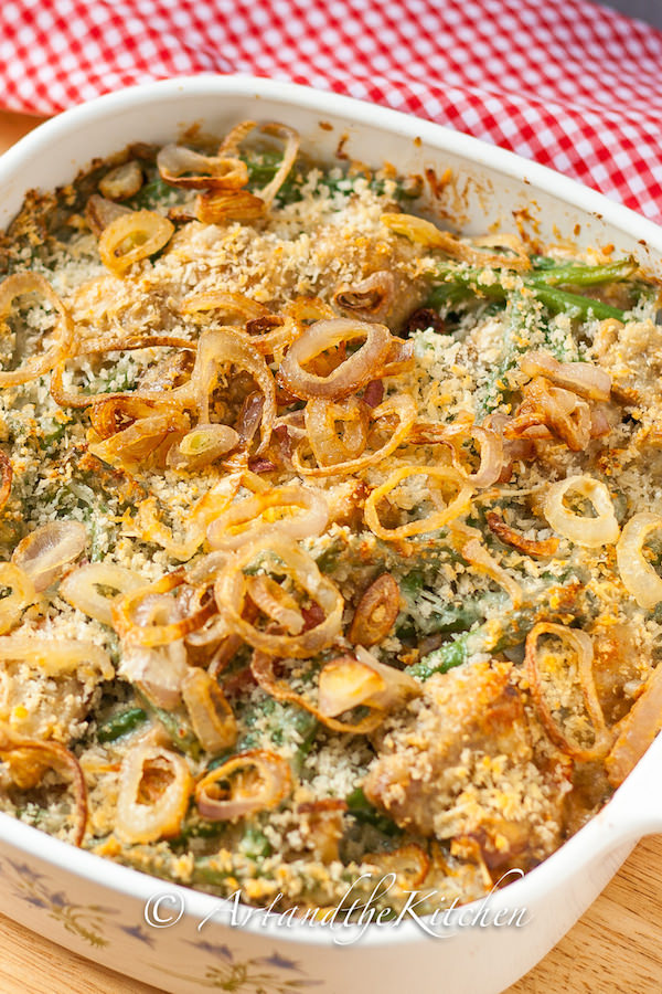 Square baking dish filled with green bean casserole topped with crunchy shallots.