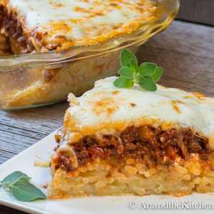 Slice of pie with layers of spaghetti, meat sauce and cheese.