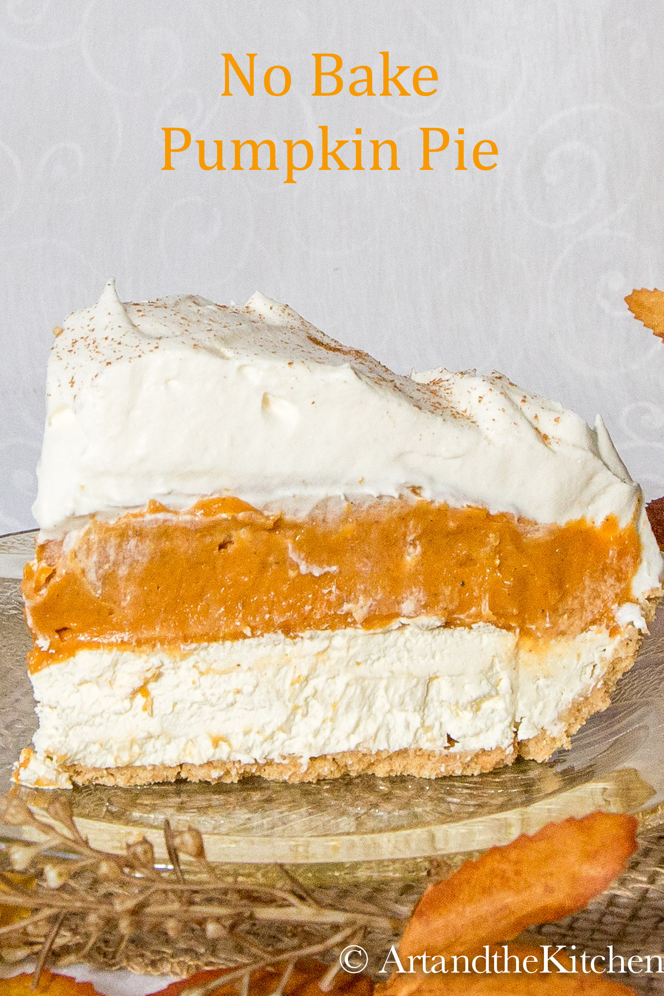 Slice of pumpkin pie with layers of pumpkin, cream cheese and whipped cream on amber coloured glass plate.