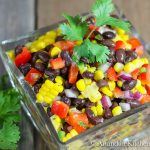 Glass bowl filled with salad of black beans, corn red , pepper, red onions and jalapeño. Garnished with parsley sprig.