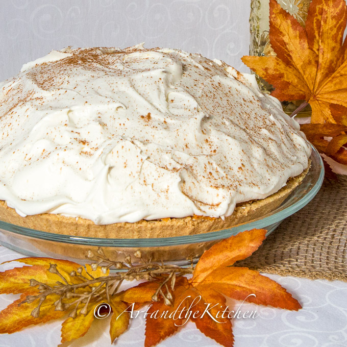 No Bake pumpkin pie topped with whipped cream, sprinkled with cinnamon with graham crust made in clear glass pie plate.
