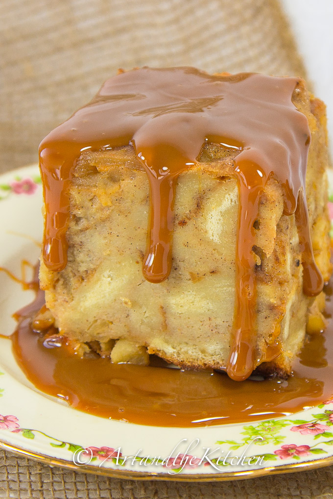 Slice of apple bread pudding covered with dulce de leche sauce on decorative plate.