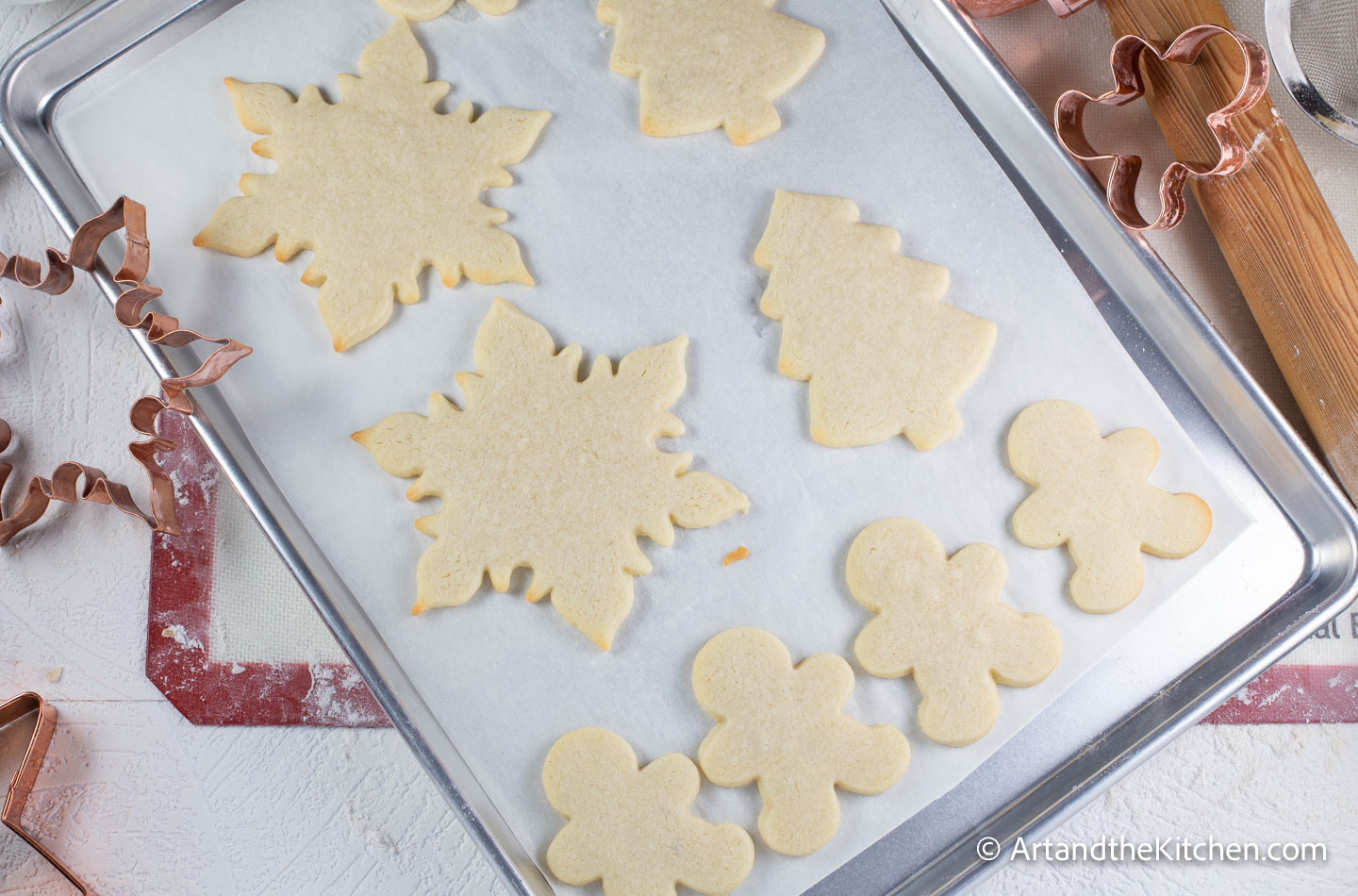 White parchment line baking pan filled with holiday shaped baked cookies.