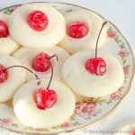 Decorative plate filled with shortbread cookies topped with maraschino cherries.