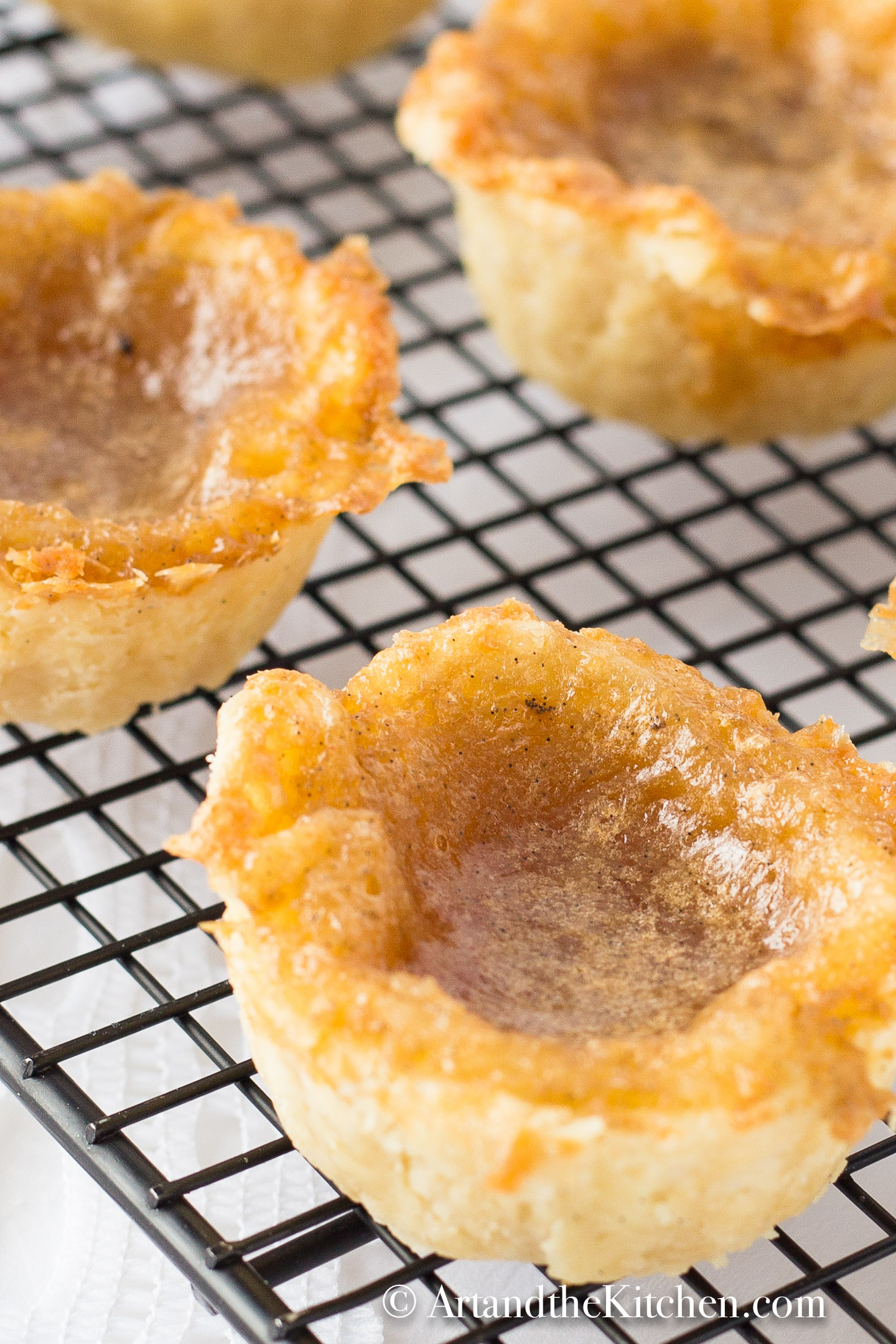 Butter tarts with flaky crust cooling on black wire rack.