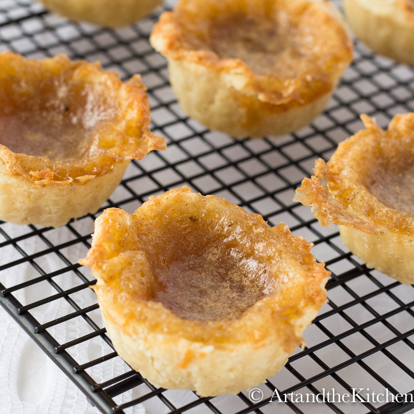homemade butter tarts on black wire cooling rack.