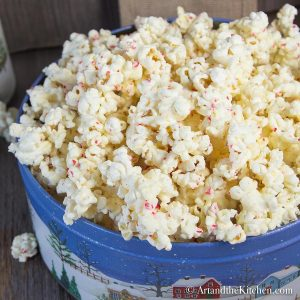 Decorative Holiday container filled with popcorn coated in white chocolate and bits of candy cane.