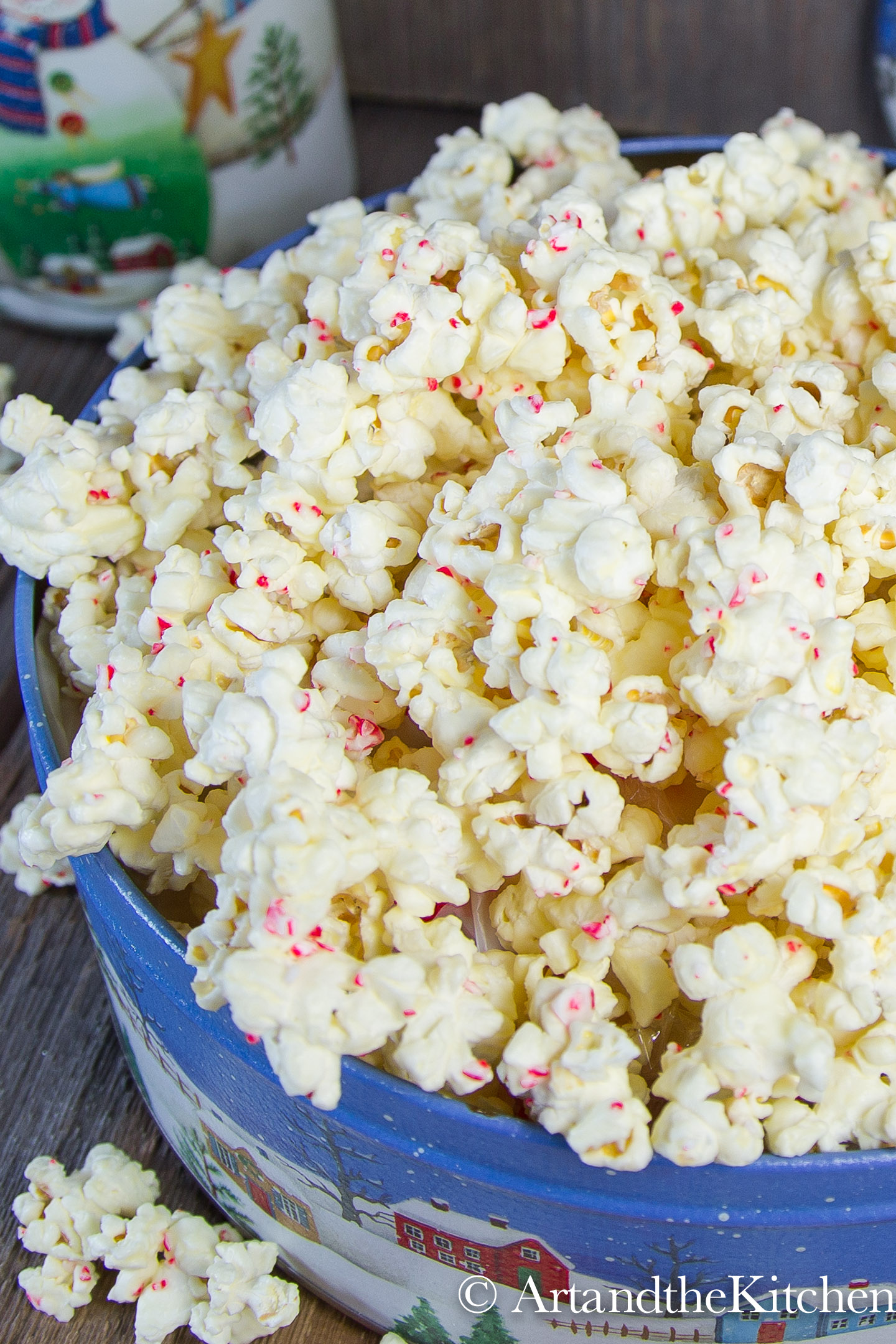 Decorative Holiday container filled with popcorn coated in white chocolate and pieces of candy cane.
