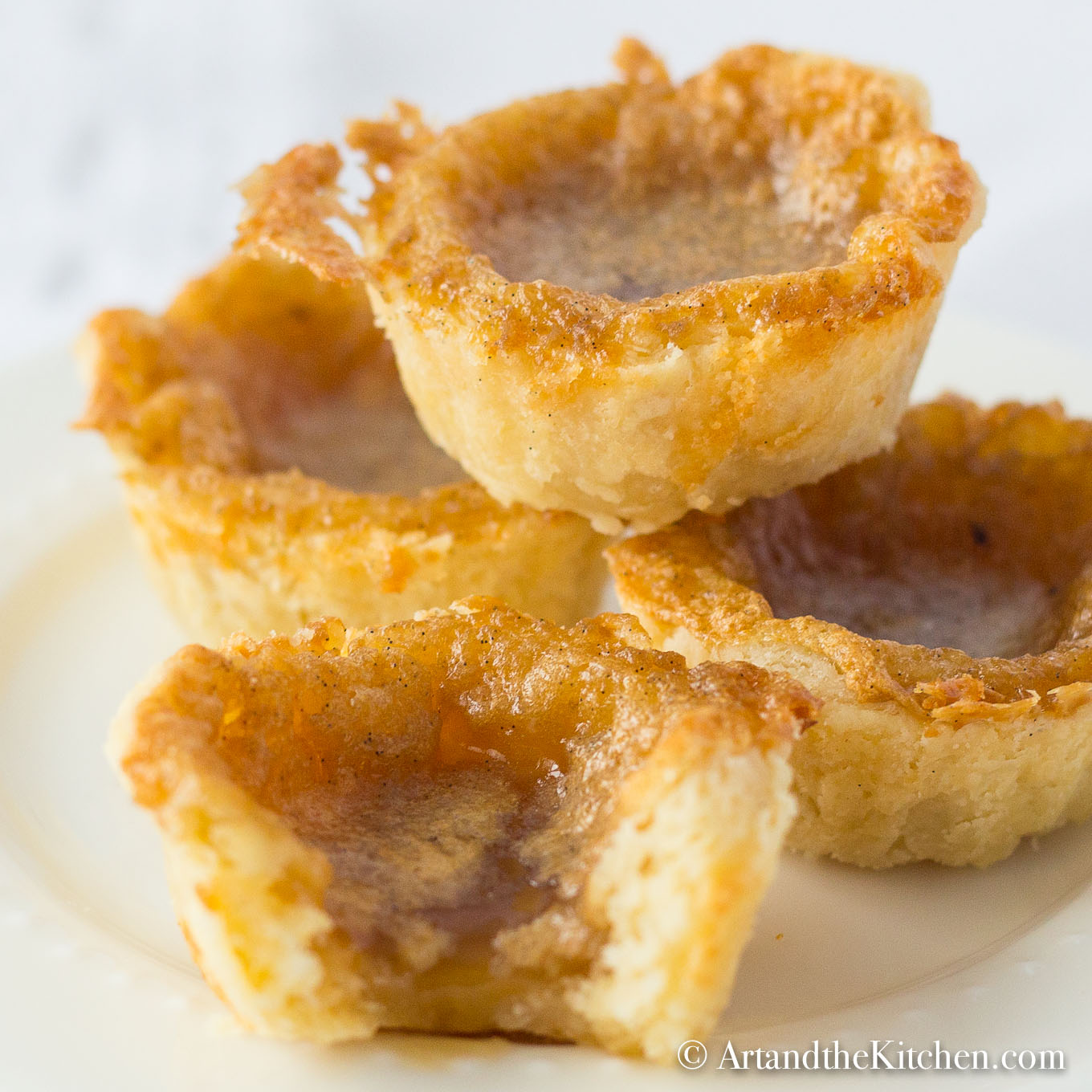 Stack of homemade butter tarts on white plate