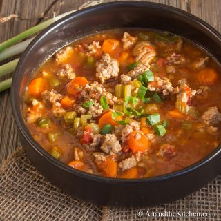 soup with chunks of ground turkey, vegetables simmered in a tomato beef broth served in a black bowl