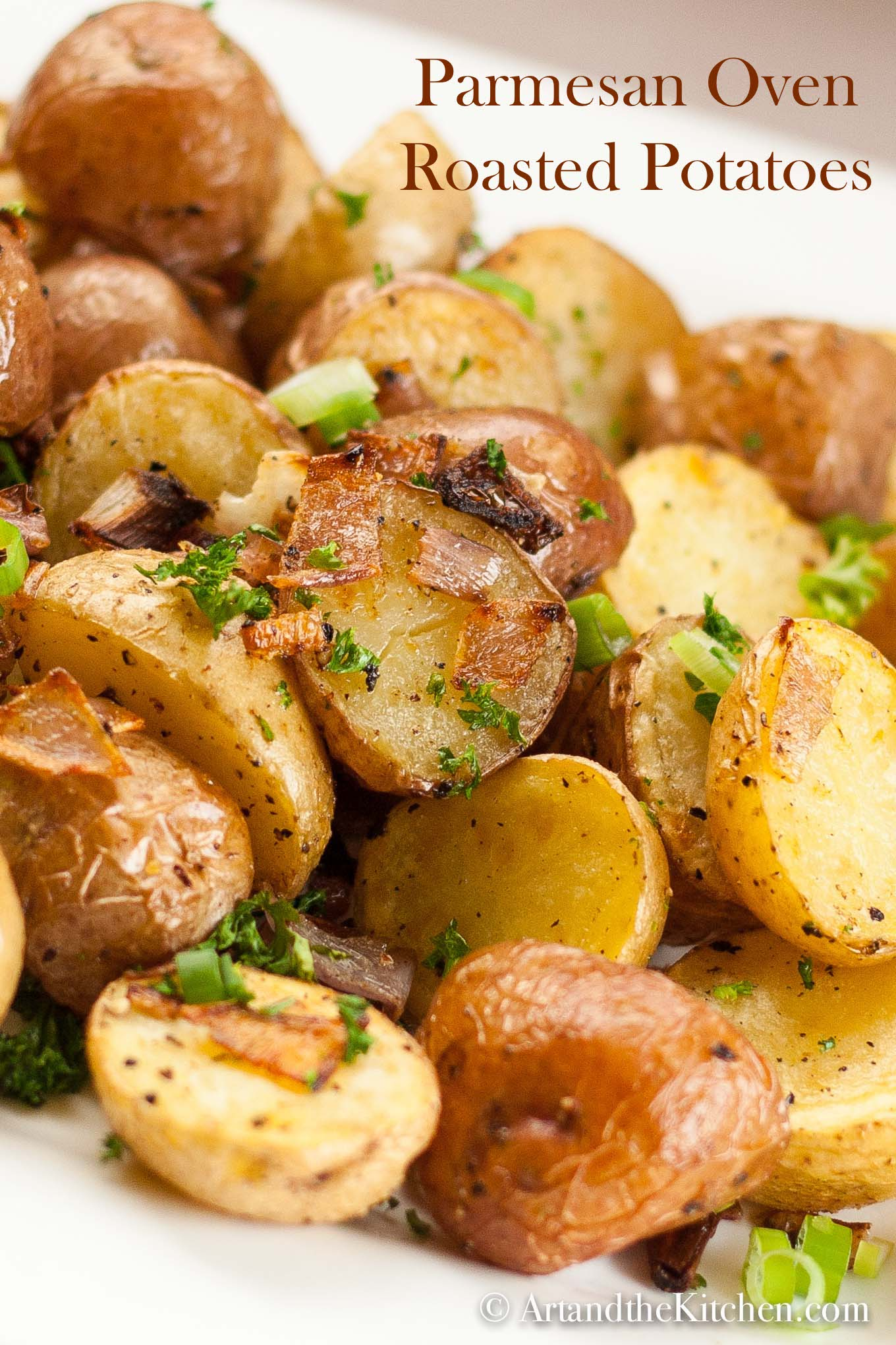 Plate of golden roasted potatoes garnished with green onions.