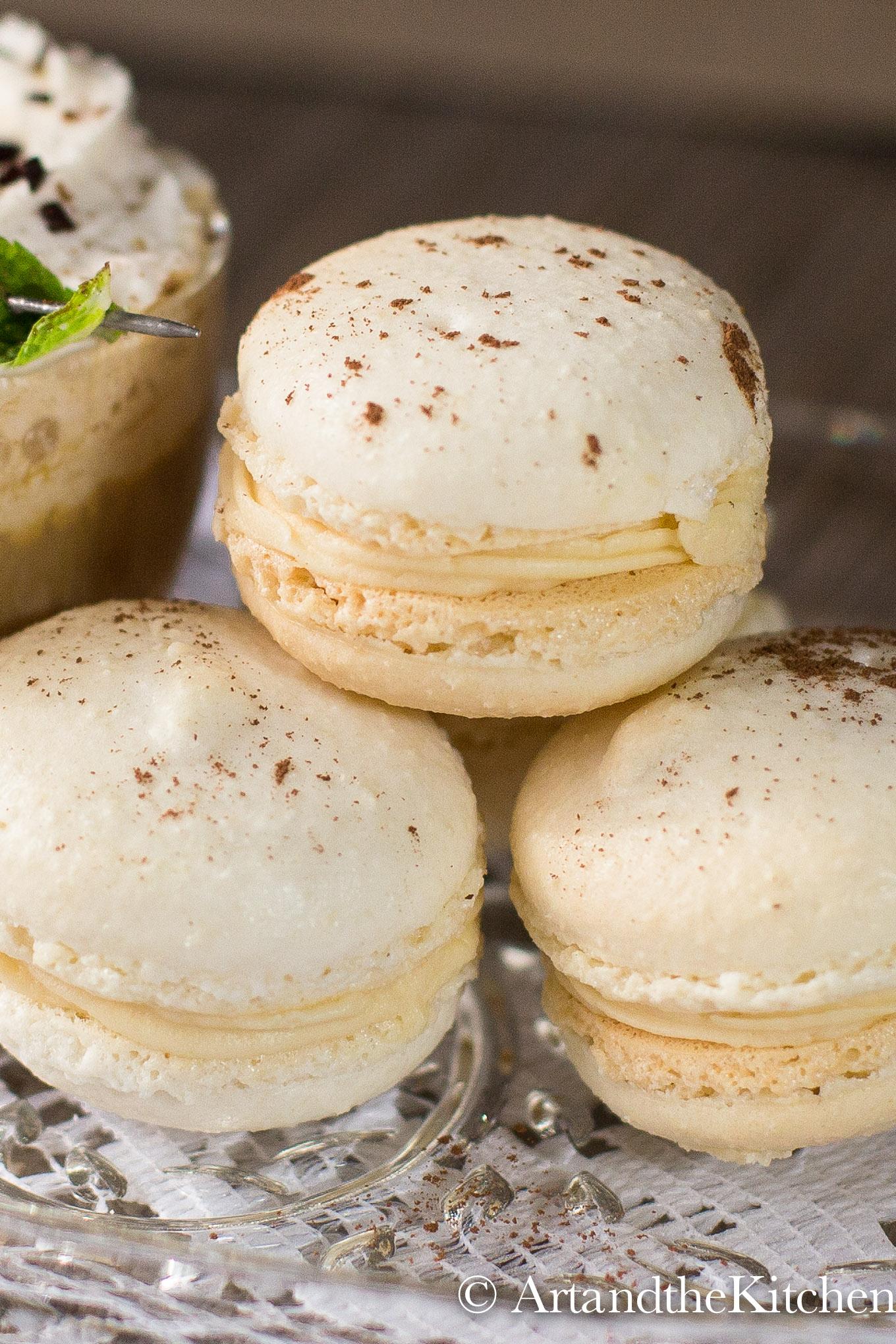 Stack of three Irish cream filled macaron cookies on glass plate.