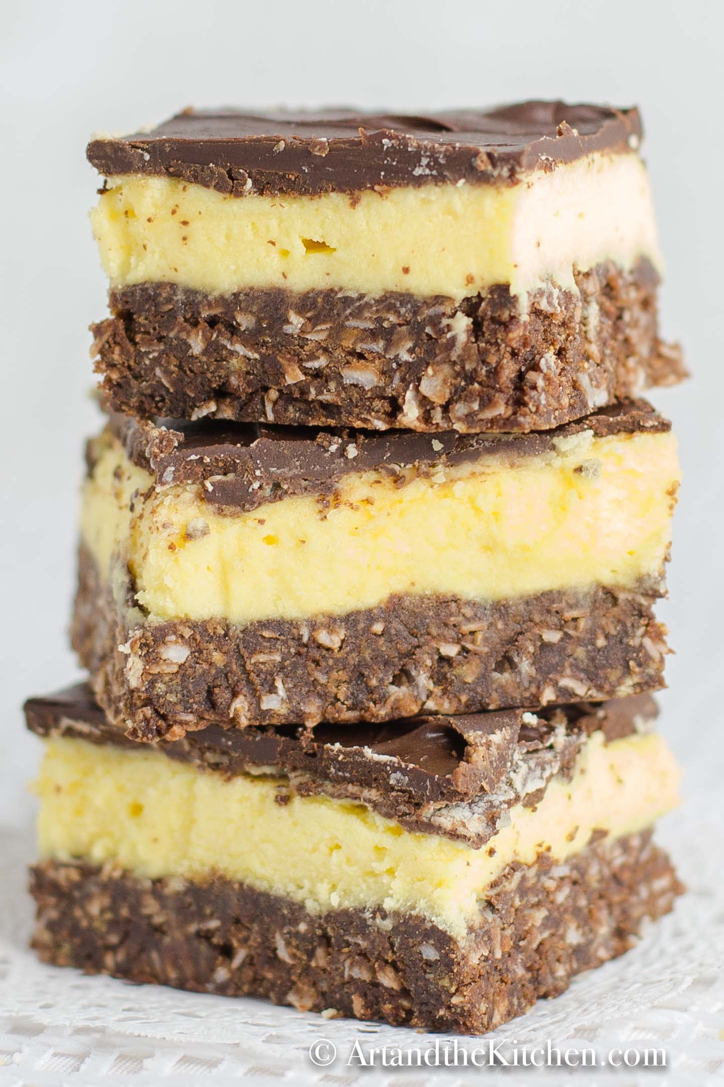 Stack of squares that have layers of chocolate, yellow custard and chocolate coconut crust.