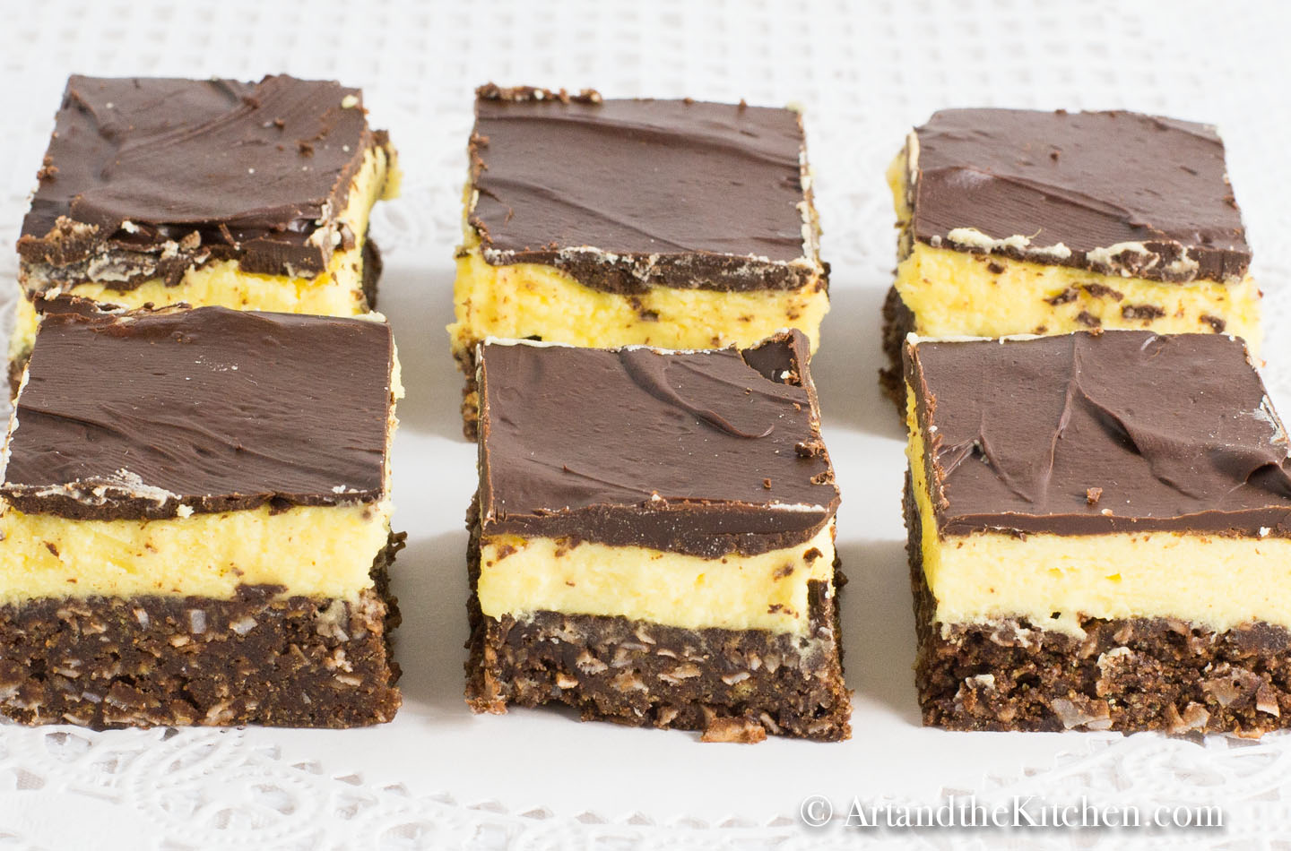 Rows of cut up squares that have layers of chocolate, yellow custard and chocolate coconut
