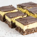 Rows of cut up squares that have layers of chocolate, yellow custard and chocolate coconut crust.