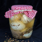Glass jar filled with pickled eggs and brine with decorative red plaid cloth covered lid.