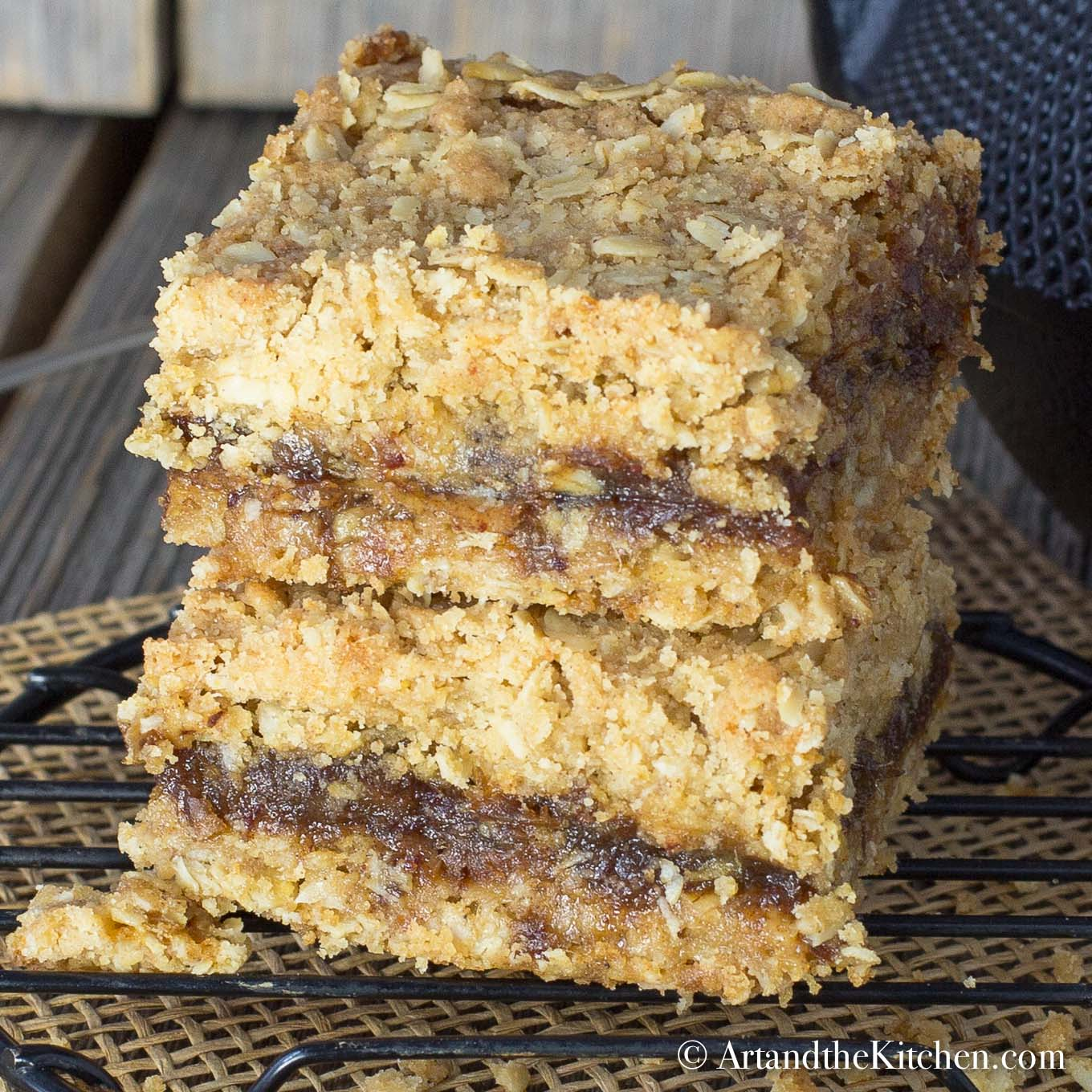 A stack of two date squares on black cooling rack.