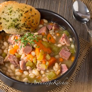 bowl of ham and bean soup with chunks of ham, navy beans, carrots and celery. Garlic bread on side of bowl, garnishes with thyme sprig.