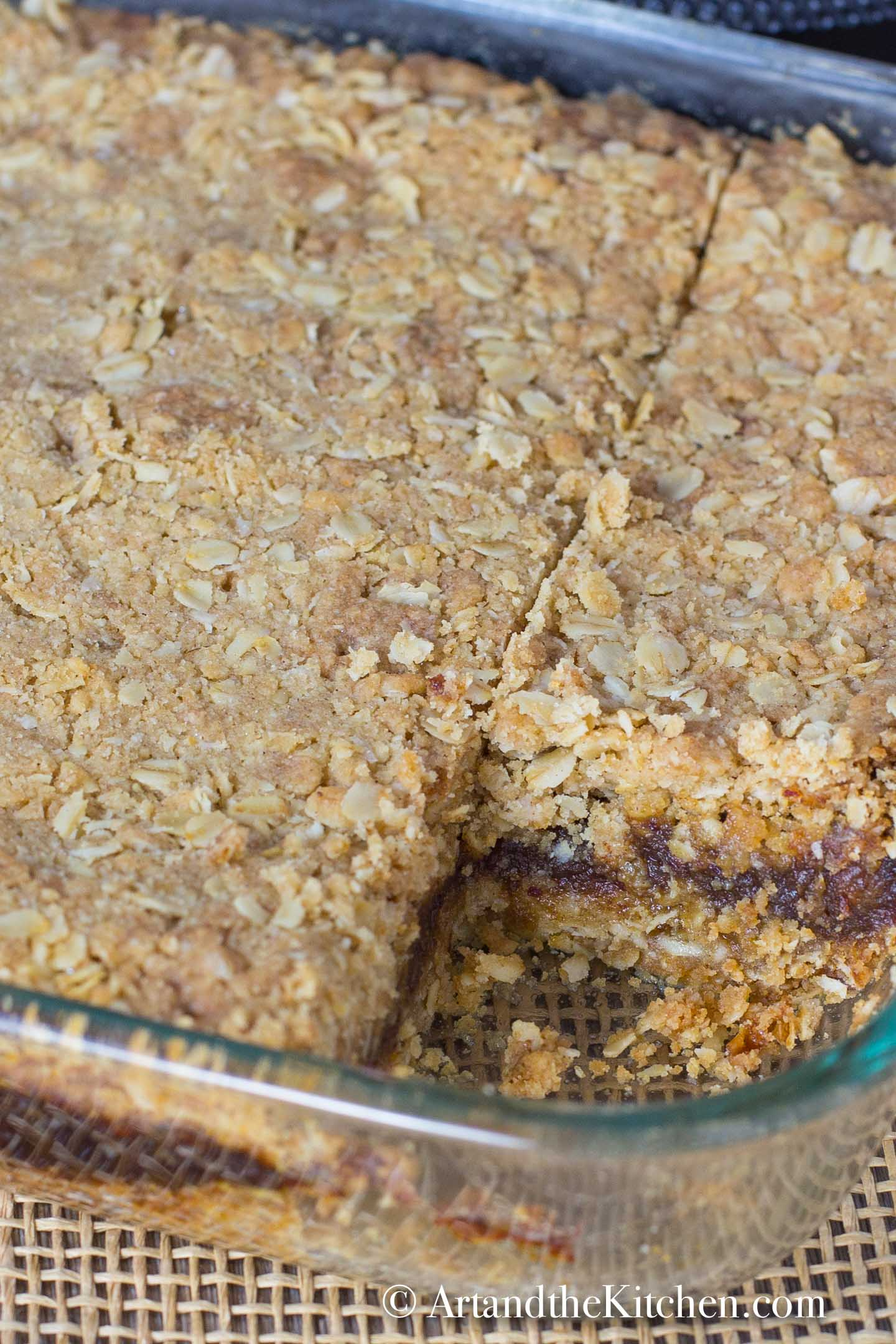 Cake pan of date squares with a slice cut out.