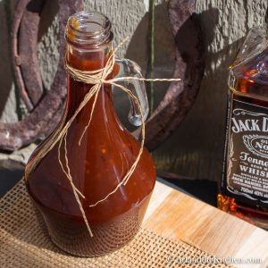 Decorative glass jar filled with homemade BBQ sauce on wood board with bottle of Jack Daniel's whiskey in background.